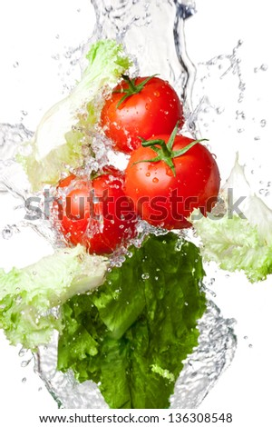Three Fresh red Tomatoes and lettuce in splash water Isolated on a white background