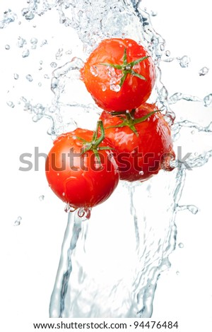 Three Fresh red Tomatoes in splash of water Isolated on white background - stock photo