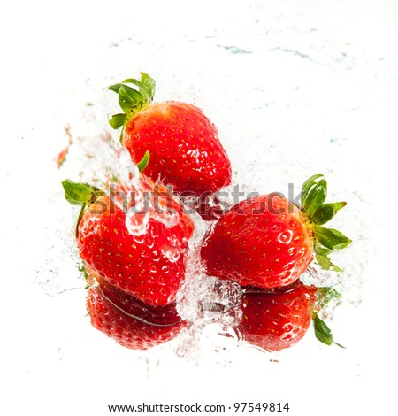 Three fresh strawberries in water splash - stock photo