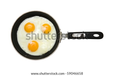 three fried unbroken eggs on black non-stick frying pan; shot from the top; isolated - stock photo