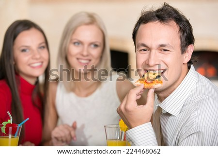 Three friends are eating a pizza and enjoying the evening. - stock photo