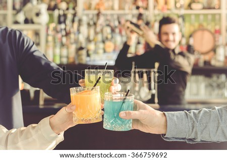 three friends are toasting with their drinks in hand during a party while the barman is shaking - people, drinks, party and lifestyle concept - stock photo