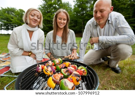 Three friends cooking shish kebabs over portable barbecue - stock photo