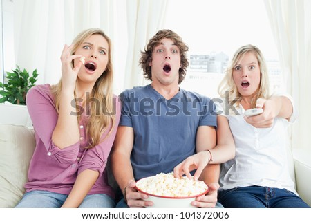 Three friends enjoying popcorn together while getting scared by the tv show - stock photo