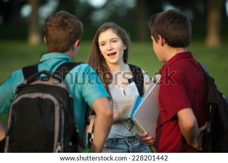 Three friends, girl and boys talking about homework outside - stock photo