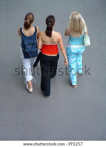 three friends (girls) walking - stock photo