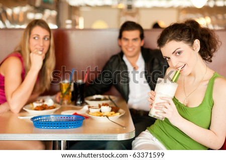 Three friends in a restaurant or diner eating fries and drinking milkshakes, shot with available light, very selective focus