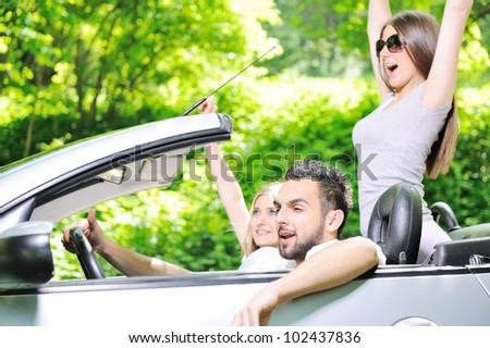 Three friends in a sports car - stock photo