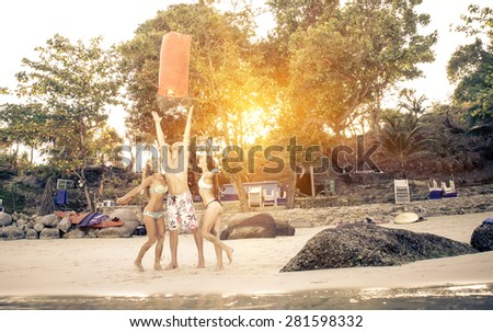three friends on the beach with lantern. they celebrate their vacation. concept about happiness and people - stock photo