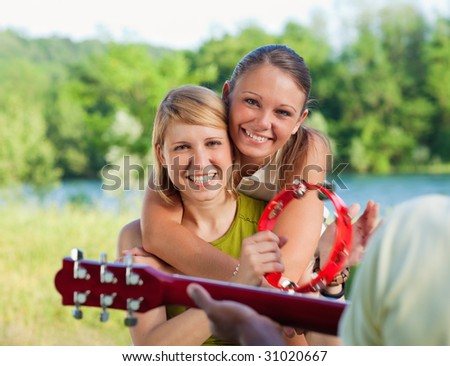 three friends playing guitar and tambourine outdoors. - stock photo