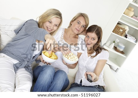 three friends sit on a white sofa and watching tv