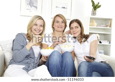 three friends sit on a white sofa and watching tv - stock photo