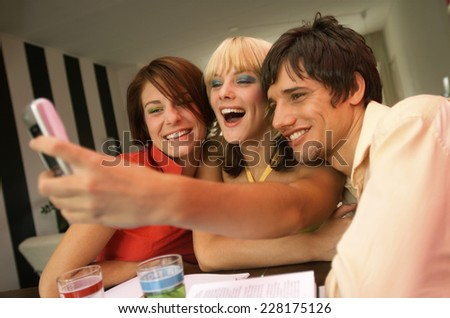 Three friends taking picture with mobile phone - stock photo