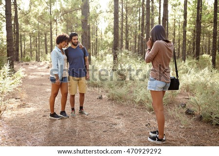 Three friends taking pictures of each other in a pine forest in the late afternoon sunshine, looking ahead while wearing casual clothing