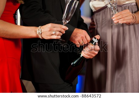 Three friends with champagne in a bar or casino - only torsos to be seen - stock photo