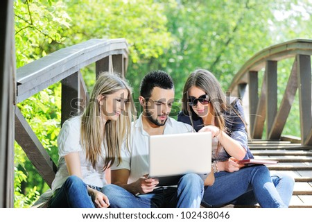 Three friends with laptop in nature - stock photo