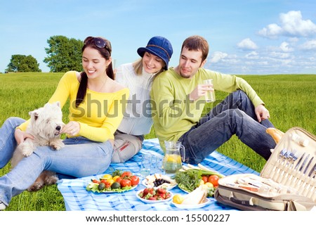 Three friends with little white dog at picnic - stock photo