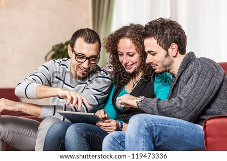 Three Friends with Tablet PC on a Sofa - stock photo