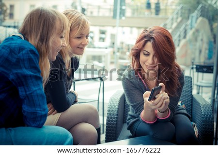 three friends woman at the bar using phone in urban contest - stock photo