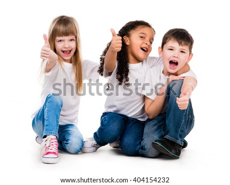 three funny children sitting on the floor with thumbs up - stock photo