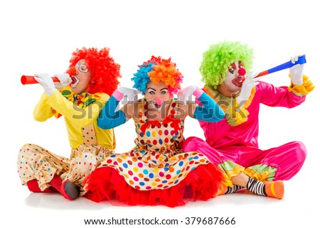 Three funny playful clowns sitting isolated on a white background. Woman in the maddle covering her ears while two men blowing horns. - stock photo