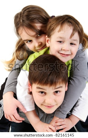 Three funny siblings, girl and boys on top of each other, studio shot against a white background. - stock photo