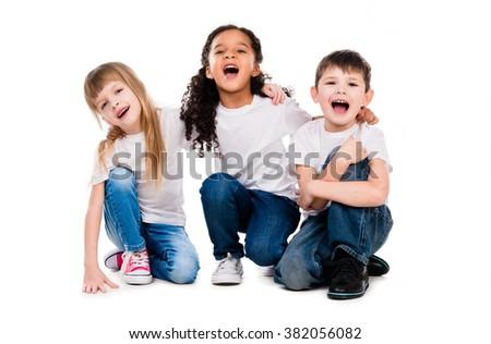 three funny trendy children laugh sitting on the floor - stock photo