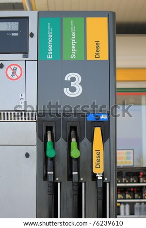 Three gas pump nozzles for gas and diesel on a petrol station - stock photo