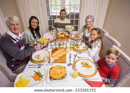 Three generation family during christmas dinner together at home in the living room - stock photo