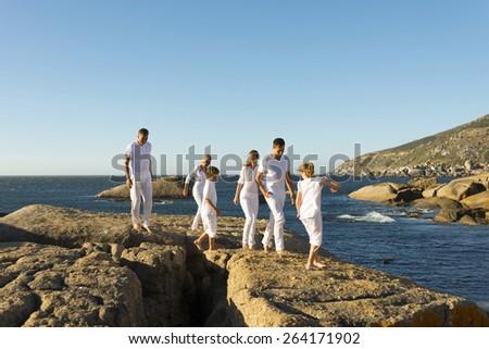 Three generation family having a walk on a rocky coast. - stock photo