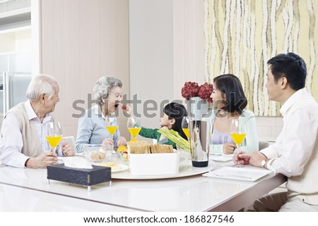 three-generation family having meal at home - stock photo