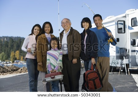 Three-generation family holding fishing poles by RV at lake - stock photo