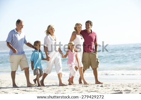 Three Generation Family On Holiday Walking On Beach - stock photo