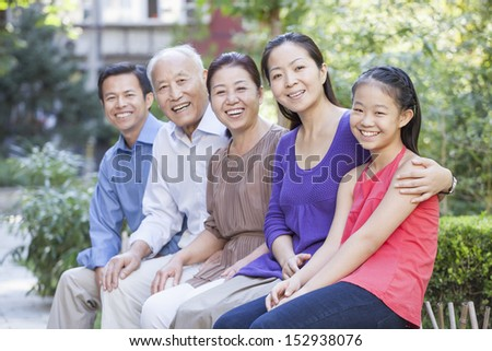 Three Generation Family Sitting in their Apartment Courtyard