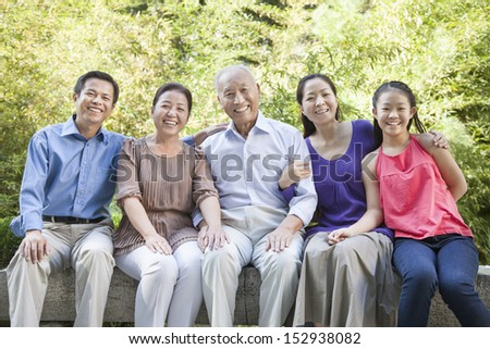 Three Generation Family Sitting in their Apartment Courtyard - stock photo