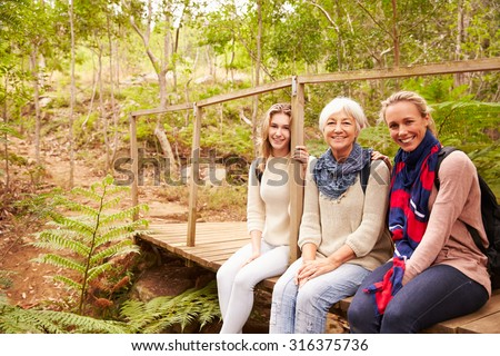 Three generations of women sitting in a forest, portrait - stock photo