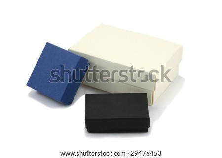 Three gift boxes of various sizes in black, blue and cream coloured cardboard, isolated on white background - stock photo