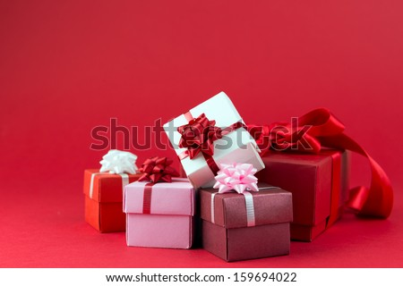 Three gift boxes wrapped with ribbons and bow isolated over red background - stock photo