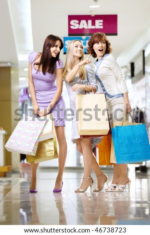 Three girl-friends to the utmost in shop show on something - stock photo