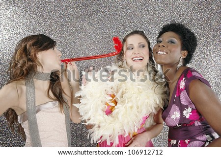 Three girls celebrating with party blowers against a silver glitter background.