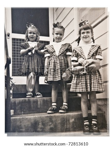 Three girls, cousins, dressed alike, at a birthday party posing for a picture on the front steps. - stock photo