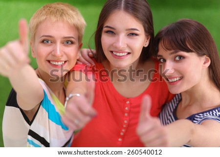 Three girls friends gesturing thumbs up  - stock photo