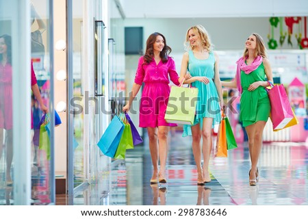 Three girls in smart dressed walking down modern mall - stock photo