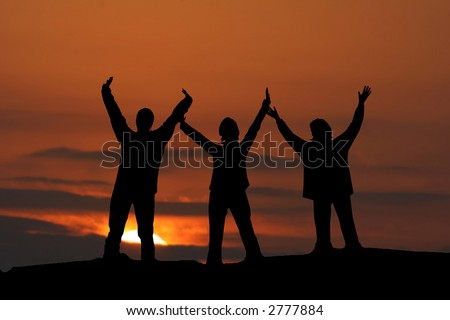 Three girls jumping up together at sunset