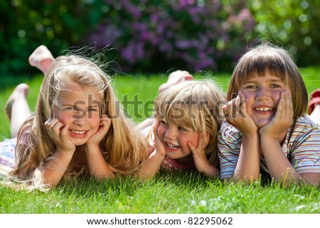 three girls lying in the grass and having fun - stock photo