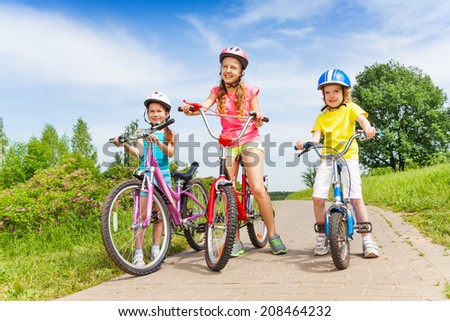 Three girls on a pave road with bicycles