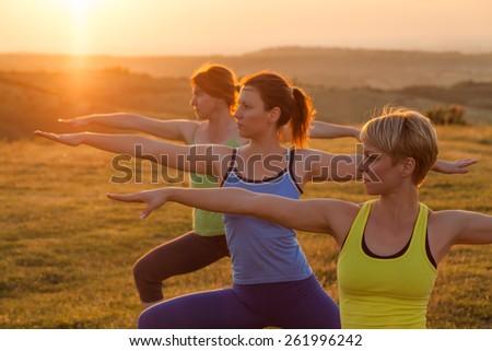 Three girls practicing yoga in sunset - stock photo