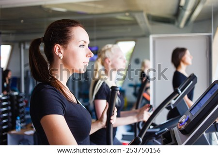 Three girls running on treadmills. - stock photo
