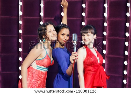 Three girls sing on the scene - stock photo