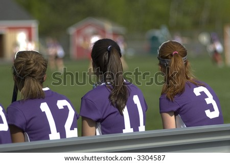 Three girls sit on the bench at a lacrosse game. - stock photo